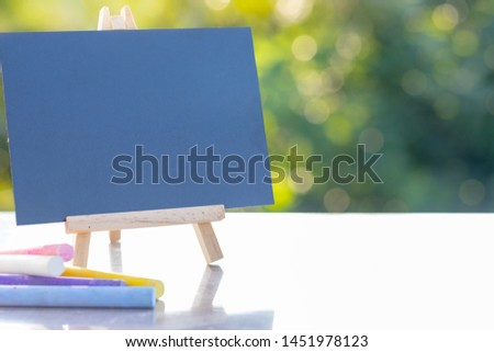 Image of empty small chalkboard on wooden easel and colorful chalk sticks over wooden table outdoor with blurred nature green background. Mock-up of menu blackboard. Blank blackboard display label. #1451978123