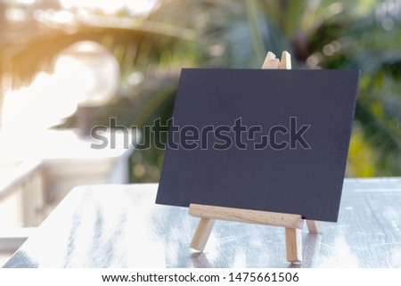 Image of empty small chalkboard on wooden easel for notes over wooden table outdoor with blurred nature green background. Mock-up of menu blackboard. Blank blackboard display label. #1475661506