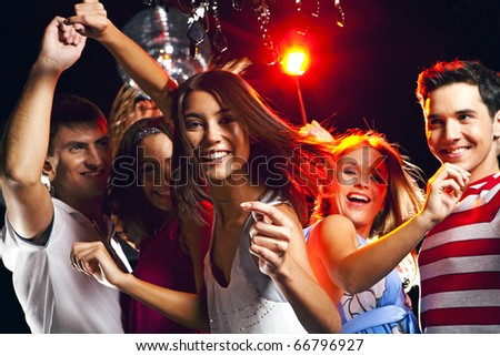 Image of energetic girl looking at camera while dancing on background of her friends - stock photo