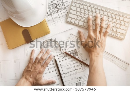 Image of engineer hands working with engineering tool on workplace top view vintage tone.