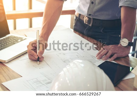 Image of engineer or architectural project, Close up of engineer's hand drawing plan on BluePrint with Engineering tools on workplace. #666529267