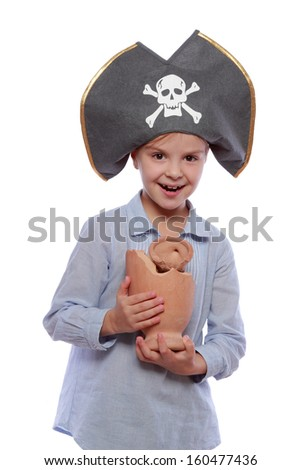 Image of European cute little girl in pirate hat holding a broken old amphora isolated on white Halloween/Beautiful smiling child dressed as a pirate with a broken amphora
