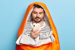 Image of European male traveler poses in orange warm sleeping bag, spends leisure time near sea, concentrated in smartphone, finds right destination poses indoor. Active hiker has rest at night.