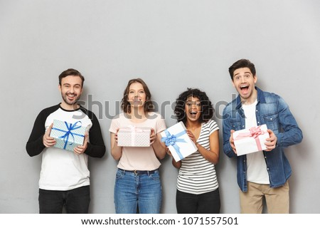 Image of excited group of friends standing isolated over grey wall background holding surprise gift boxes. #1071557501