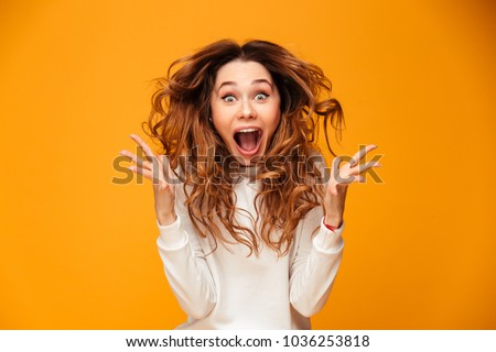 Image of excited screaming young woman standing isolated over yellow background. Looking camera.