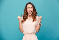 Image of excited young lady standing isolated over blue background make winner gesture.