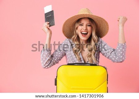 Image of excited young pretty woman tourist posing isolated over pink wall background with suitcase holding passport with tickets make winner gesture.