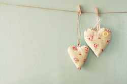 image of fabric hearts hanging on rope in front of blue wooden background. retro filtered
