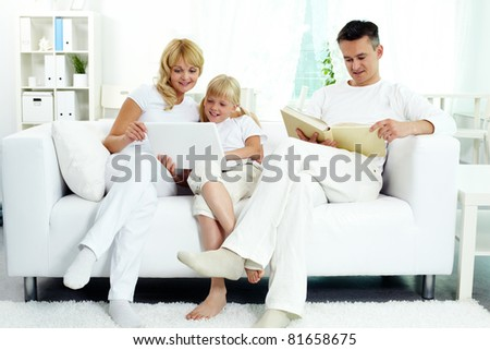 Image of family sitting on the sofa and spending free time at home - stock photo