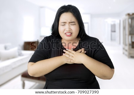 Image of fat woman having a heart attack while touching her chest and standing in the living room