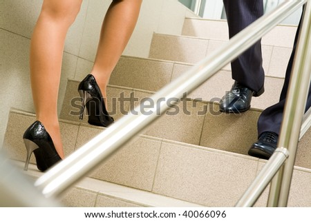 Image of female and male legs going along marble ladder in office building