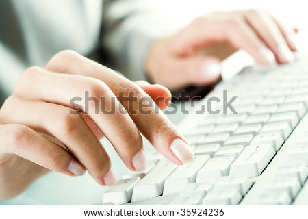 Image of female fingers pressing computer keys at workplace