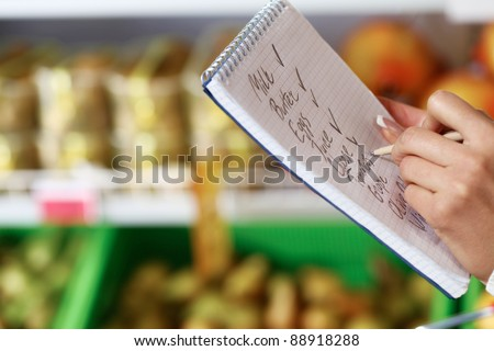 Image of female hand with pen holding product list while buying goods in supermarket