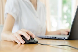 Image of female hands clicking computer mouse
