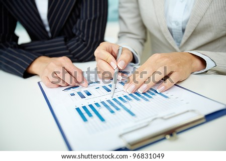 Image of female hands with pens over business document at meeting