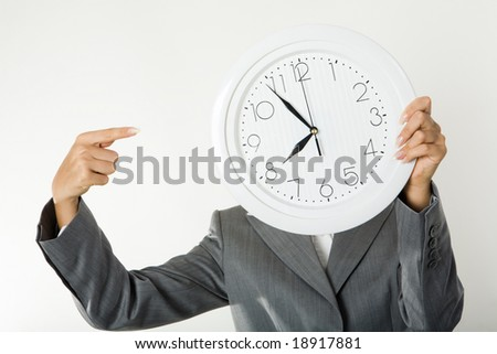 Image of female?s hands holding clock in front of face and pointing at it