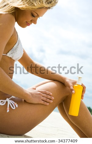 Image of female with suncare lotion sitting on sandy beach