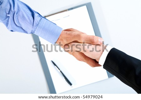 Image of final of deal over paper with pen