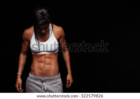 Image of fitness woman in sports clothing looking down. Young female model with muscular body. Horizontal studio shot with copy space on black background.