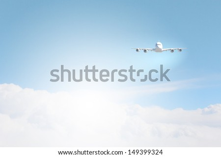 Image of flying airplane in clear sky with sun at background
