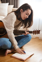 Image of focused beautiful woman playing guitar and composing song while sitting on floor in living room