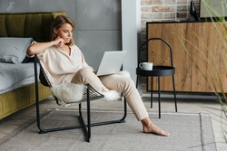Image of focused blonde nice woman in stylish pajamas working with laptop while sitting on armchair at living room