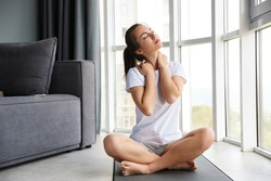 Image of focused young woman stretching her neck while sitting on yoga mat near window indoors