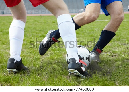 Image of footballers legs kicking soccer ball on stadium