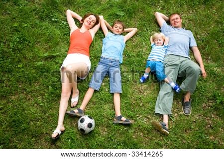 Image of four people lying on the grass together