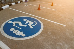 Image of free space blue point of cars parking area with wheelchair or disable person-elderly people-pregnant woman sign or symbol shown on outdoor concrete floor with sunlight lighting background.