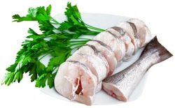 Image of fresh raw steaks of hake fish with greens on plate. Isolated over white background