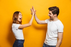 Image of friendly young people man and woman in basic clothing laughing and giving high five isolated over yellow background