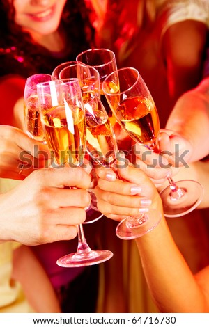 Image of friends hands with crystal glasses full of champagne