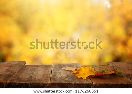 image of front rustic wood table with dry gold leaves and fall bokeh background
