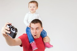 Image of funny father and child making selfie at vintage camera, white background. Fashion baby. Looking at camera. Hobby.