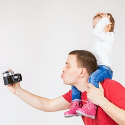 Image of funny father and child making selfie at vintage old camera. Family. White background. Fashion baby. Looking at camera. Hobby.