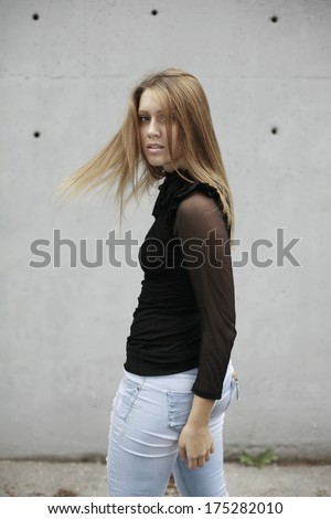 image of girl in white shirt and red scarf around the neck sitting on the fence looking  down