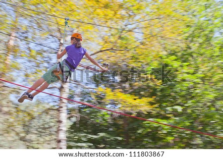 Image of girl swinging fast on the rope swing tied to a tree in mountain helmet and safety equipment.