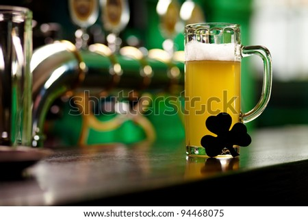 Image of glass of beer with shamrock leaf on pub table