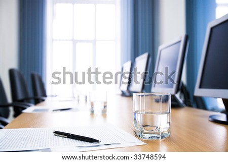 Image of glass of water on workplace with paper, pen and monitors near by