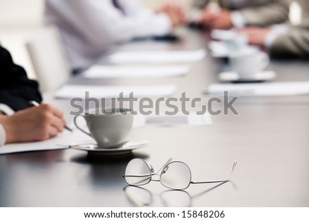 Image of  glasses placed on the table during a seminar