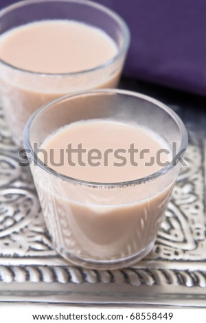 Image of glasses with Indian chai tea in silver and violet colors.