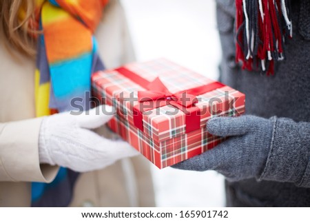 Image of gloved hand of guy giving his girlfriend Christmas present