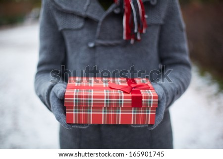 Image of gloved hands of guy holding Christmas present