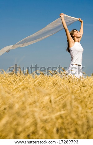 Image of golden wheat on the background of enjoying woman