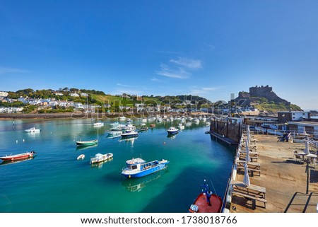 Image of Gorey Harbour with fishing and pleasure boats, the pier bullworks and Gorey Castle in the background with blue sky. Jersey, Channel Islands, UK Stock photo ©