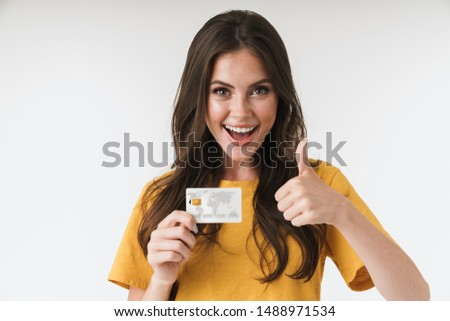 Image of gorgeous brunette woman wearing casual clothes showing thumb up and holding credit card isolated over white background