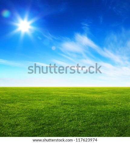 Image of green grass field and bright blue sky - stock photo