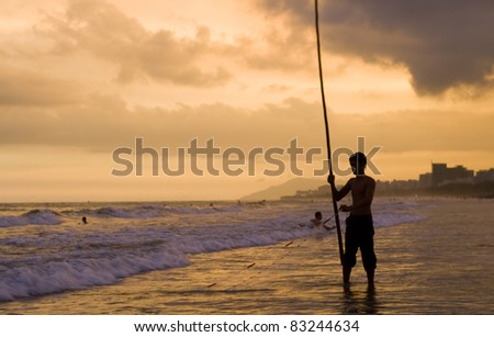 Image of Hainan young fisher gathering the net on the beach at sunset. Some people are swimming on the background.