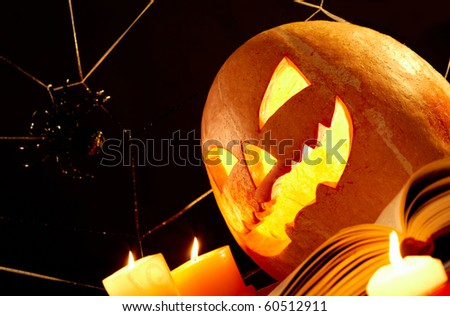 Image of Halloween pumpkin with burning candles and cobweb with spider near by